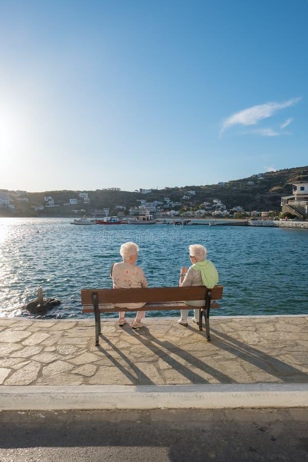 Entretiens supérieurs non identifiés de dames au banc de bord de mer dans le village pittoresque de Batsi sur l'île d'Andros images libres de droits