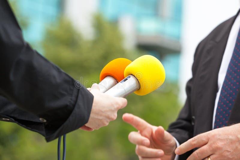 Entrevista de los medios del reportero que conduce de sexo femenino con el hombre de negocios o el político foto de archivo libre de regalías