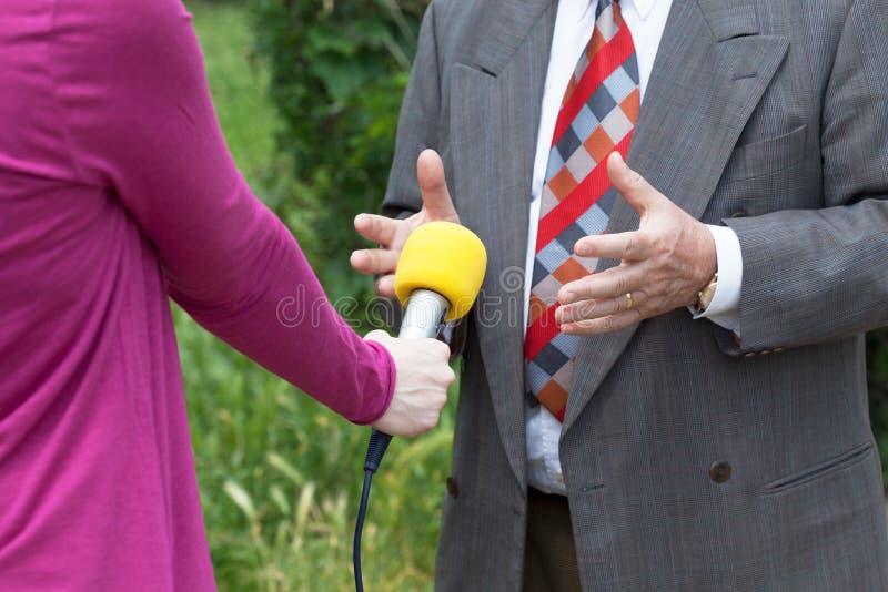 Entrevista de los medios Micrófono amarillo imagenes de archivo