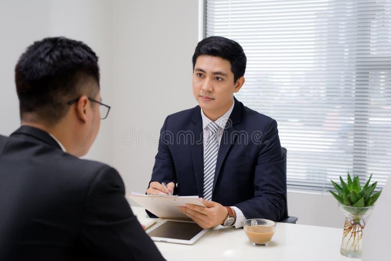 Entrevista de trabajo de dos profesionales del negocio Saludo de nuevo collea imagen de archivo