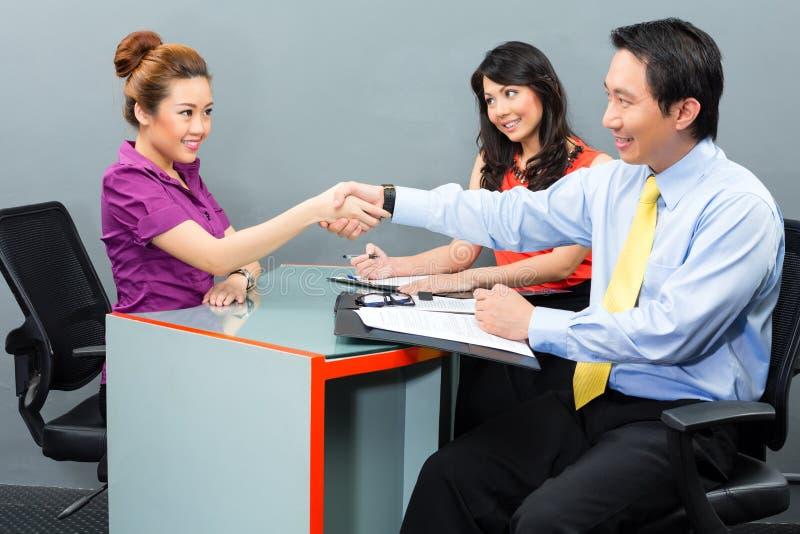 Entrevista de trabajo para un nuevo empleo o alquiler en oficina asiática imagenes de archivo