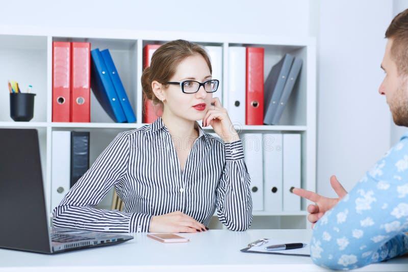 Entrevista de trabajo - reclutador que hace preguntas El jefe femenino joven habla con el buscador de trabajo fotos de archivo libres de regalías