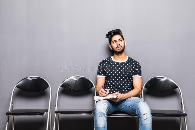 Entrevista de trabalho de espera do homem indiano novo no salão da recepção foto de stock royalty free