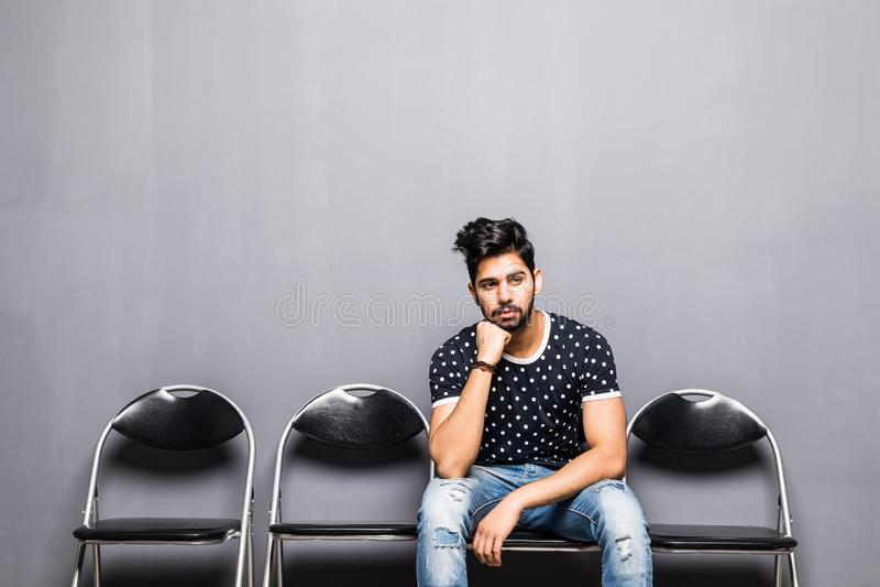 Entrevista de trabalho de espera do homem indiano novo no salão da recepção imagens de stock