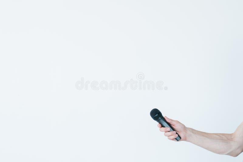 Entrevista do mic da posse da mão do homem do jornalismo dos mass media fotografia de stock