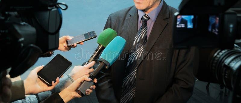 Entrevista, informe, medio El hombre abstracto en un traje y un lazo habla a las cámaras de vídeo del reportero y Las manos femen foto de archivo libre de regalías