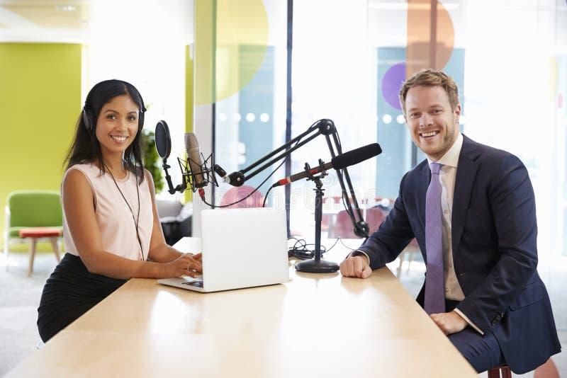 Entrevistador fêmea e convidado em um estúdio que sorriem à câmera foto de stock royalty free