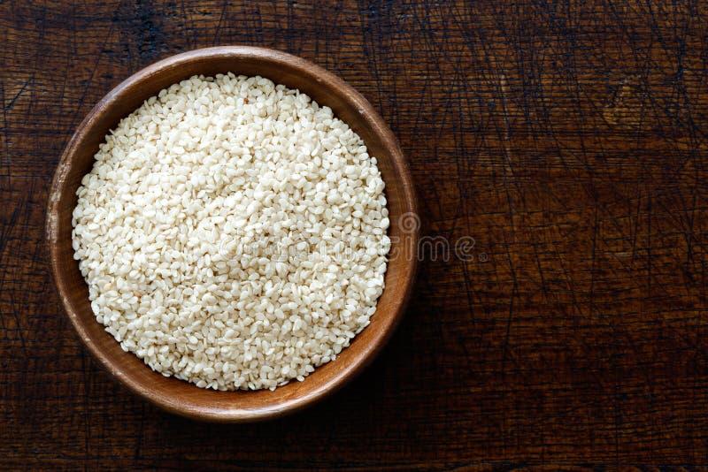 Entrindete Samen des indischen Sesams in der dunklen hölzernen Schüssel lokalisiert auf dunklem b lizenzfreies stockfoto