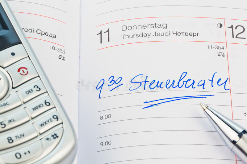 Entry in the calendar: tax consultant. An appointment is entered in a calendar: tax consultant stock photo