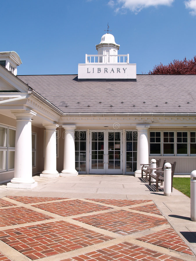 Entry doors to a library by a brick sidewalk stock images