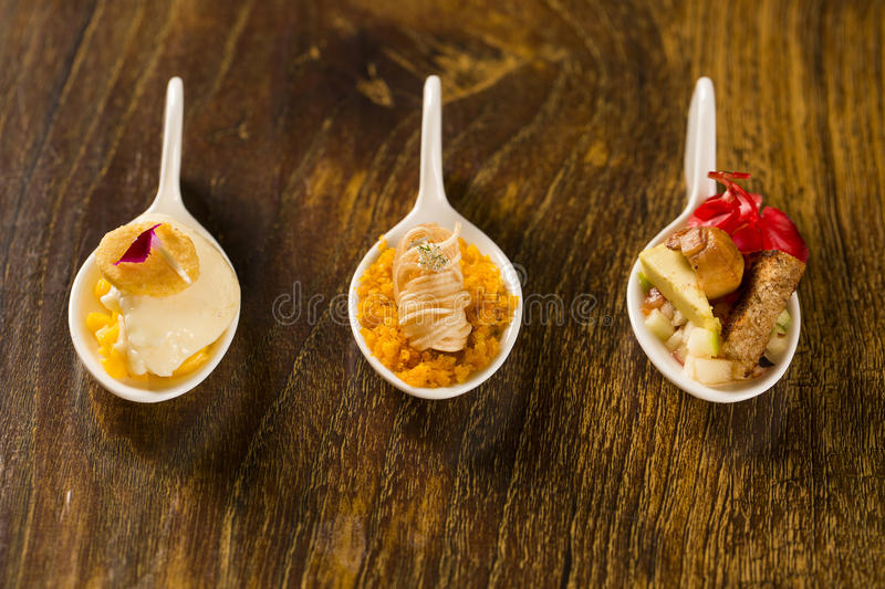 Entry, entree and dessert of finger food in a spoon. royalty free stock image