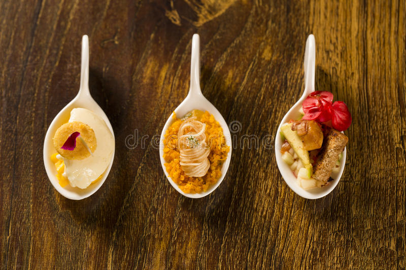 Entry, entree and dessert of finger food in a spoon. royalty free stock images