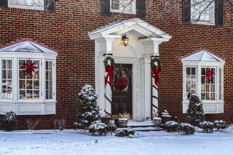 Entry and porch to traditional Georgian style brick house with columns and bay windows decorated for Christmas in the snow stock image