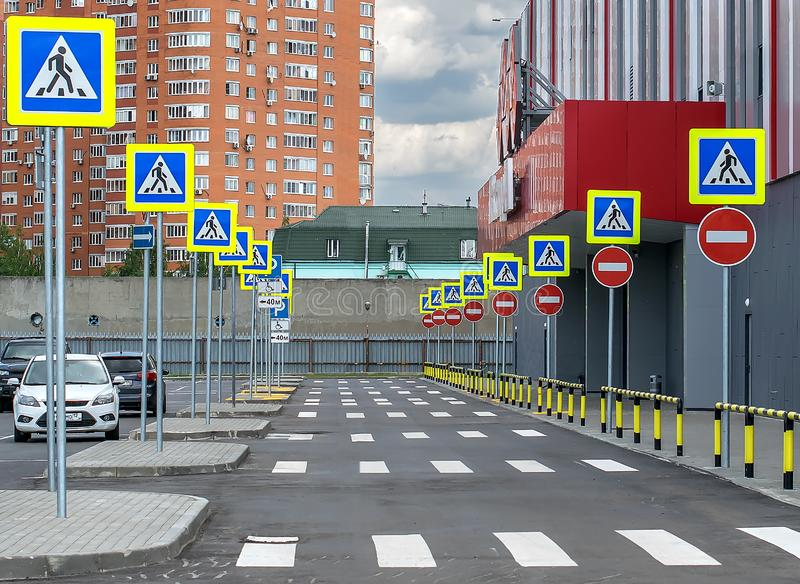 Entry prohibited road marking zebra and many road traffic signs pedestrian crossing street and parking stock images