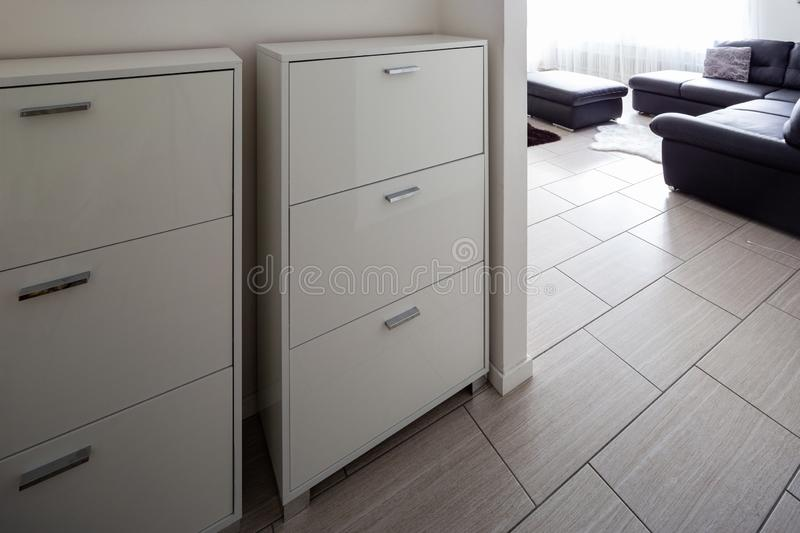 Entry with shoe rack in the house with white walls stock photography