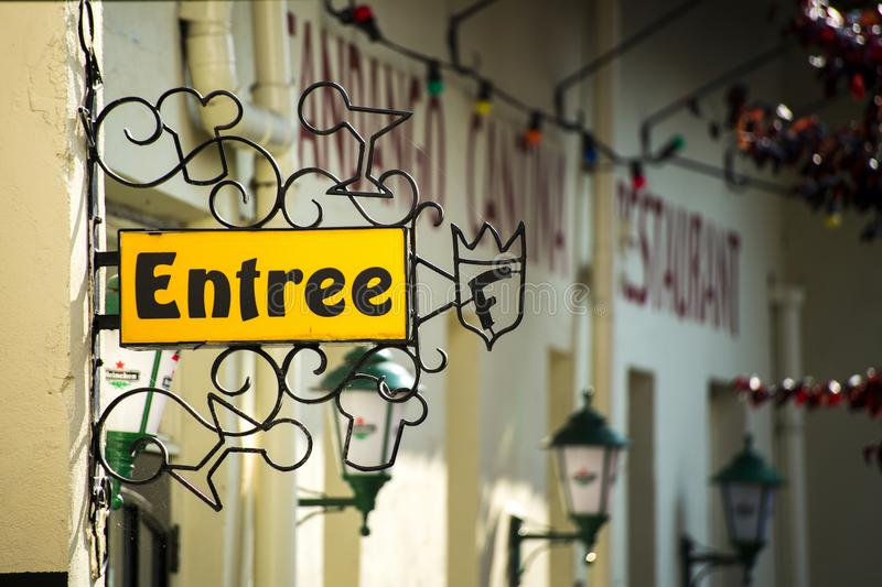 A entry sign saying ``Entree`` on a yellow sign stock images