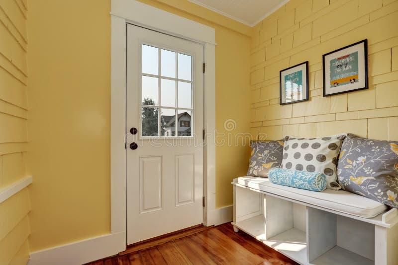 Entryway z kolor żółty ścianami i składowa ławka w bielu zdjęcie stock