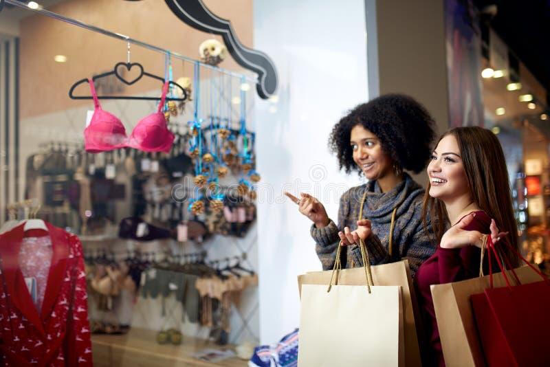 Entscheiden das glückliche multiethnische junge Fraueneinkaufen der Mischrasse zwei für Wäsche nahe Kleidungsboutiquen-Geschäftsf lizenzfreies stockbild