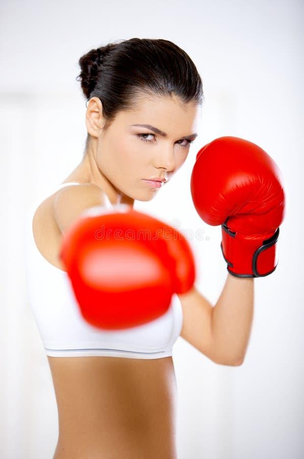 Entschlossene Frau, die rote Boxhandschuhe trägt stockfoto