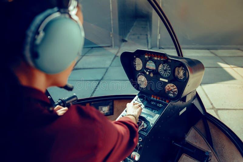 Entschlossener erfahrener weiblicher Pilot, Informationen über Armaturenbrett beobachtend stockfoto