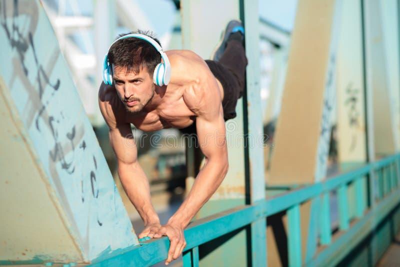 Entschlossener geeigneter junger Mann, der StoßUPS auf einem Stahleisenbahnbrückenzaun tut lizenzfreie stockbilder