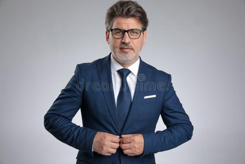 Entschlossener Geschäftsmann, der seine Jacke justiert stockfoto