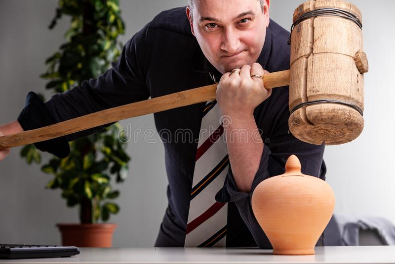 Entschlossener Mann, der einen großen hölzernen Holzhammer hält stockfoto