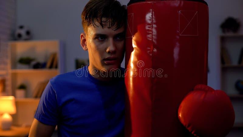 Entschlossener selbstbewusster Jugendlicher, der Sandsack nach intensivem Training umarmt stockbild