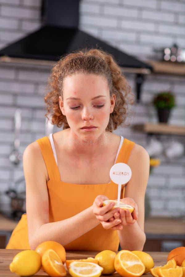 Entschlossenes verärgertes Mädchen, das nahe dem Küchentisch bedeckt mit Zitronen und Orangen bleibt lizenzfreie stockbilder