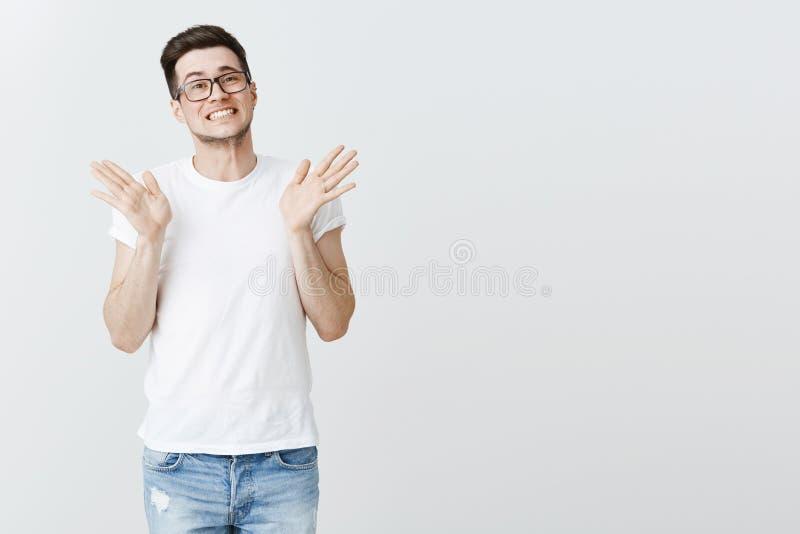 Entschuldigender hübscher junger männlicher Mitarbeiter in den Gläsern, die Hände nahe Schultern anheben und mit intensivem traur stockbild