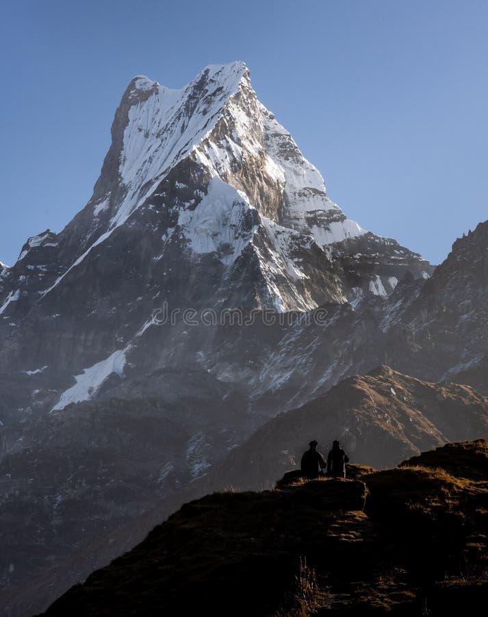 Entsetzende Ansicht der Fisch-Endstückspitze und zwei Trekkers so gesehen von Mardi Himal-Trekking stockbild
