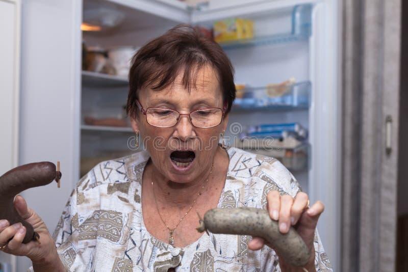 Entsetzte ältere Frau, die Schweinefleischleberwürste hält stockfotografie