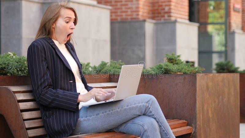 Entsetzte aufgeregte Geschäftsfrau, die den Laptop, sitzend außerhalb des Büros verwendet stockfotografie