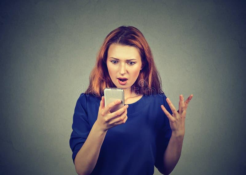 Entsetzte aufpassende Nachrichten der Frau auf Smartphone lizenzfreies stockfoto