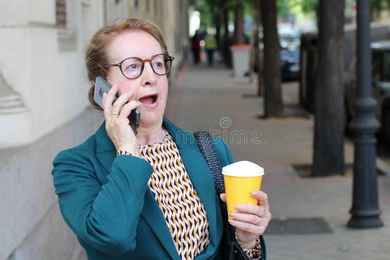 Entsetzte Dame am Telefon drau?en lizenzfreie stockfotos