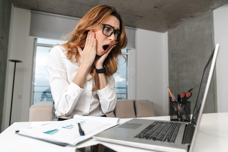 Entsetzte emotionale Geschäftsfrau zuhause gekleidet im Abendtoilettehemd unter Verwendung der Laptop-Computers stockfotos
