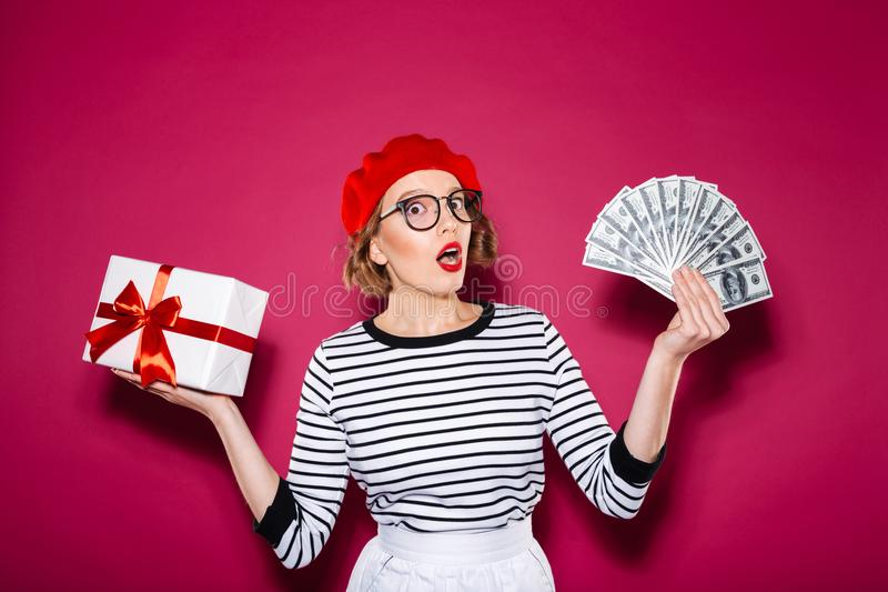 Entsetzte Frau in den Brillen, die zwischen Geschenkbox und Geld wählen lizenzfreie stockfotos
