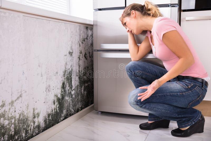 Entsetzte Frau, die Form auf Wand betrachtet lizenzfreie stockfotos