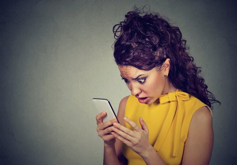Entsetzte Frau, die Handy mit Quergesichtsausdruck betrachtet stockfotografie