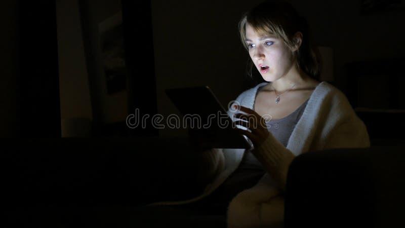 Entsetzte Frau, die Tablet nachts, wundernd verwendet lizenzfreies stockfoto