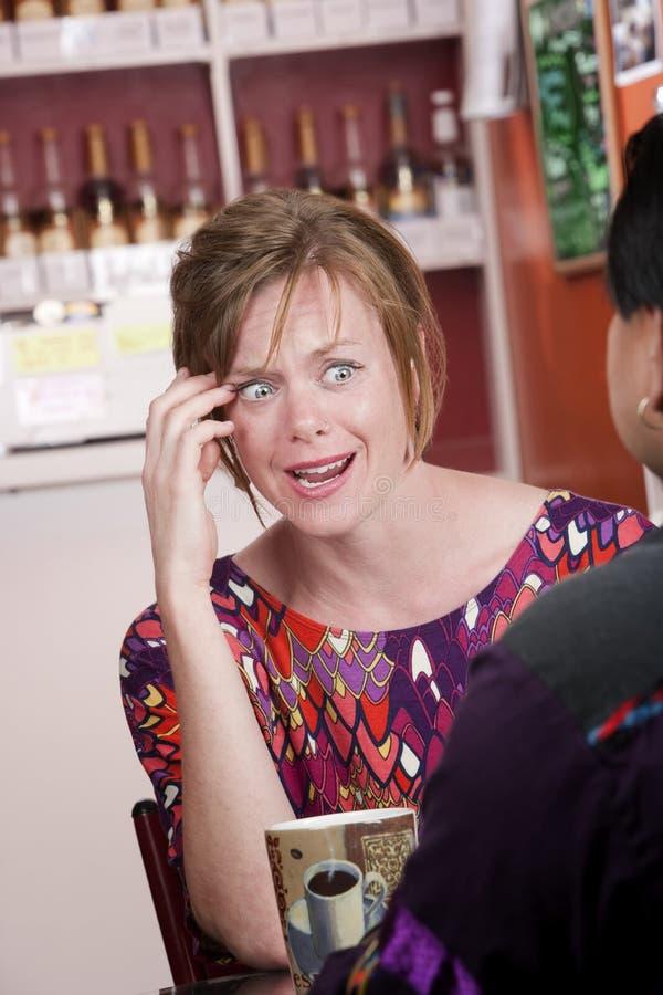 Entsetzte Frau im Kaffeehaus mit männlichem Freund lizenzfreie stockfotos