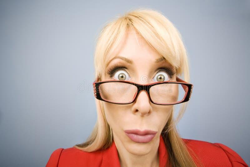 Entsetzte Frau im Rot, das ein lustiges Gesicht bildet stockbilder