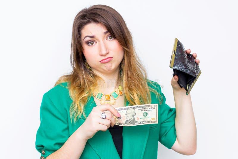 Entsetzte Geschäftsfrau, die in der grünen Jacke ohne Geld, Frau mit Geldbörse ohne Geld nur $ 10 trägt stockbild