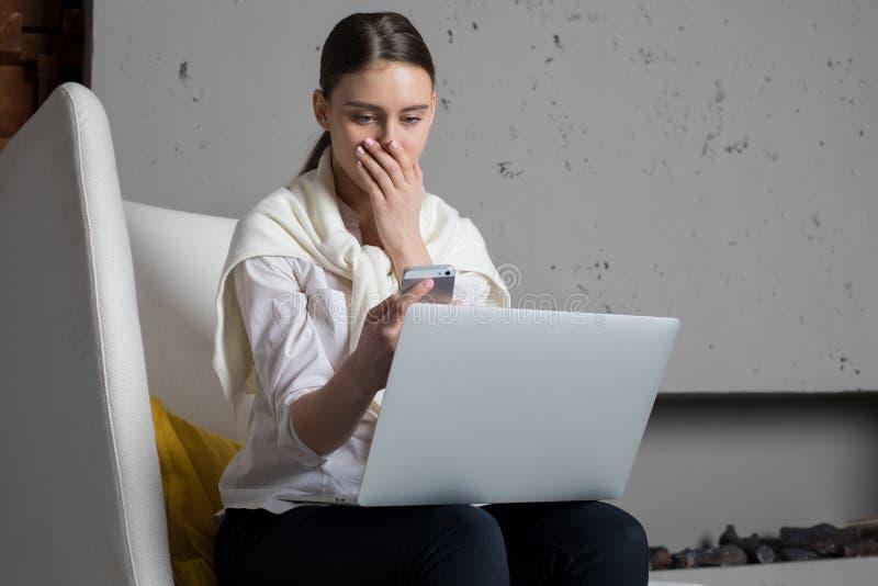 Entsetzte Geschäftsfrau wurde Nachrichten am Handy über die Nichterfüllung der Firma während ihr Sitzen mit Laptop-Computer herei stockfotos