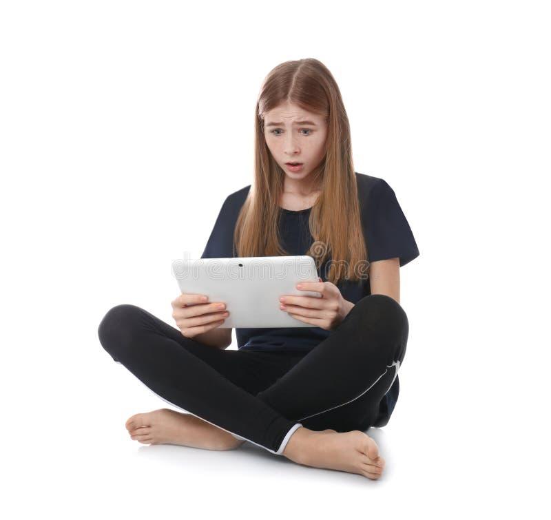 Entsetzte Jugendliche mit Tablette auf weißem Hintergrund lizenzfreie stockfotografie