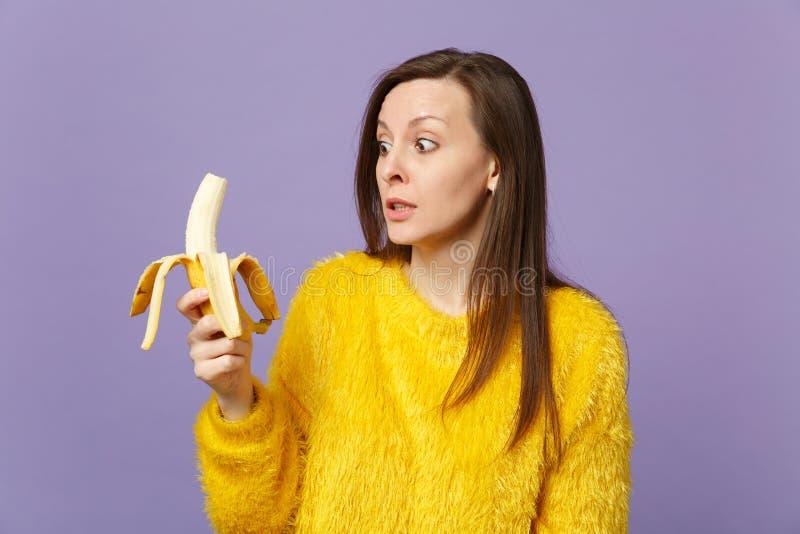 Entsetzte junge Frau in der Pelzstrickjacke, die in der Hand, schauend auf der frischen reifen Bananenfrucht lokalisiert auf viol lizenzfreie stockfotografie