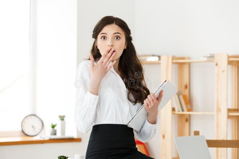 Entsetzte junge Geschäftsfrau überrascht durch lesende unerwartete Nachrichten im Dokument, überraschtes FrauenBüroangestelltgefü stockfotografie