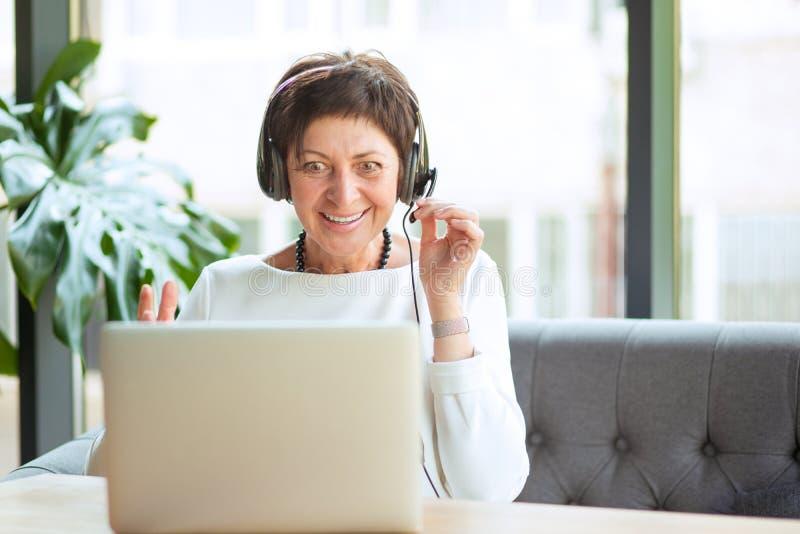 Entsetzte reife Frau, die Computer betrachtet lizenzfreie stockfotos