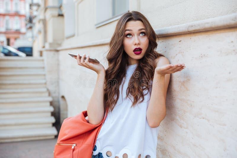 Entsetzte schöne junge Frau, die draußen ihren Smartphone hält stockbild