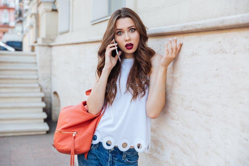 Entsetzte schöne junge Frau, die draußen ihren Smartphone hält stockfoto